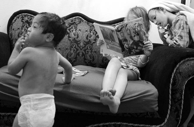 Henry, 3, watches television as Almalinda, 7, and Maria, 5, read a book at home in Las Vegas on Wednesday, November 28, 2012.