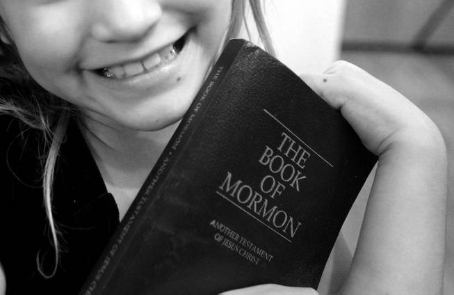 Almalinda Gonzales, 7, shows off her copy of The Book of Mormon at her home in Las Vegas on Wednesday, November 28, 2012.