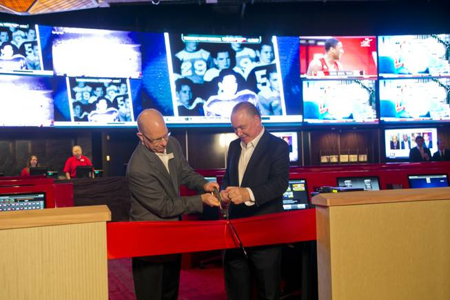 Kirk Golding, VP of Information Technology for Silverton, at left, and Lee Amaitis, President & CEO Cantor Gaming, cut the ceremonial ribbon during the grand opening of The Cantor Sports Book at Silverton, Thursday, Nov. 29, 2012. The 2,000 square-foot sports book features a 2.35 million LED pixel video screen that can show four feature sporting events at once.