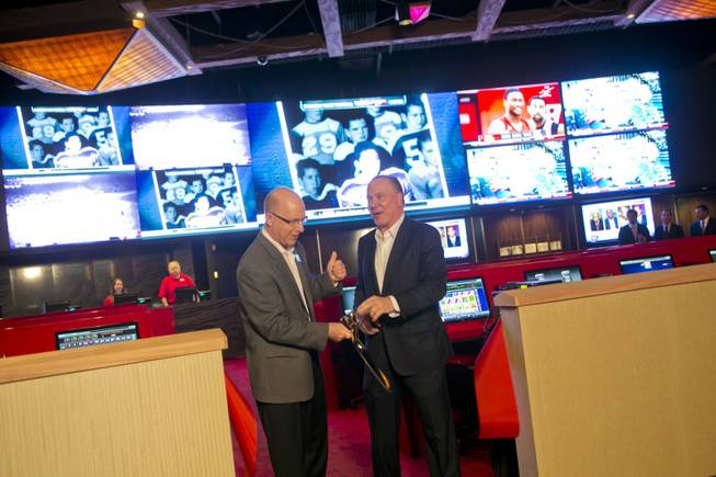 Kirk Golding, VP of Information Technology for Silverton, at left, and Lee Amaitis, President & CEO Cantor Gaming, cut the ceremonial ribbon during the grand opening of The Cantor Sports Book at Silverton, Thursday, Nov. 29, 2012. The 2,000 square-foot sports book features a 2.35 million LED pixel video screen that can show 4 feature sporting events at once.