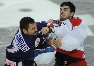 Adam Huxley, right, throws a right hand towards the face of Mike Liambas during a third period fight on Saturday night.