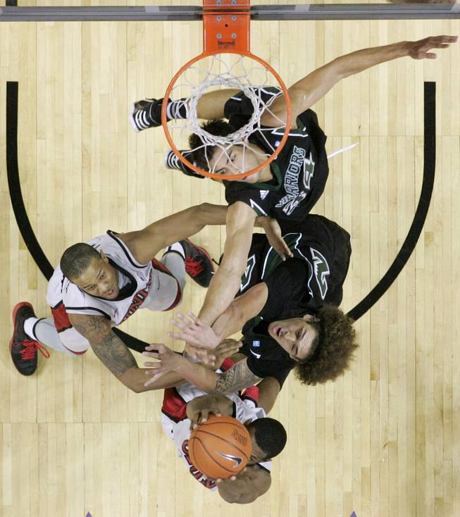 UNLV guard Anthony Marshall grabs a rebound from Hawaii forward Isaac Fotu and guard Michael Harper, top, during their game Saturday, Dec. 1, 2012 at the Thomas & Mack. UNLV won 77-63