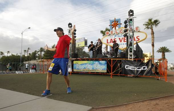 A runner stops to have his photo taken in front of the Welcome To Las Vegas sign during the Zappos.com Rock 'n' Roll Las Vegas Marathon Sunday, Dec. 2, 2012. The band Drive performs behind him.