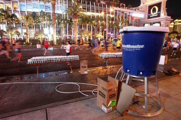 Race workers hand out water during the Zappos.com Rock 'n' Roll Las Vegas Marathon Sunday, Dec. 2, 2012.