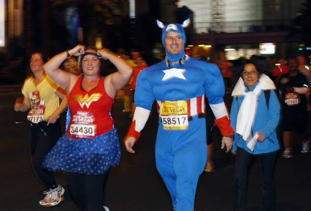 Runners dressed as Wonder Woman and Captain America make their way northbound on the Las vegas Strip during the Zappos.com Rock 'n' Roll Las Vegas Marathon Sunday, Dec. 2, 2012.