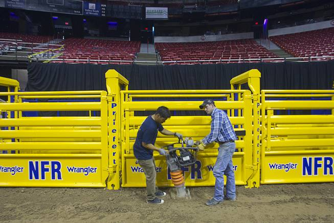 Adrian Torres, left, and Josh Jordan use an impact rammer to compact dirt around the bull chutes as they prepare the Thomas & Mack Center for the National Finals Rodeo Sunday, Dec. 2, 2012. This year's NFR begins Thursday, Dec. 6 and runs through Saturday Dec. 15.