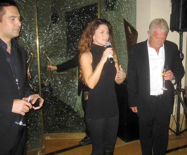 Shania Twain is flanked by Raj Kapoor and John Meglen as she makes remarks at her