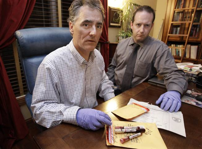 In this photo taken Friday, Nov. 30, 2012, in Chicago, Cook County Sheriff Tom Dart, left, and sheriff's detective Jason Moran are photographed with three recently discovered vials of mass murderer John Wayne Gacy's blood.