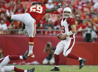 Arizona Cardinals quarterback John Skelton (19) dodges Kansas City Chiefs linebacker Jovan Belcher (59) during the first half of an NFL pre-season football game in Kansas City, Mo., Friday, Aug. 10, 2012.