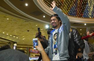 Filipino boxer Manny Pacquiao waves to fans as he leaves the lobby of the MGM Grand Tuesday, December 4, 2012. Pacquiao will take on Juan Manuel Marquez of Mexico in a welterweight bout at the MGM Grand Garden Arena on Saturday. It will be the fourth time for the boxers to fight each other.