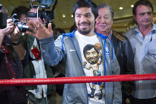 Filipino boxer Manny Pacquiao waves to fans after arriving at the MGM Grand Tuesday, December 4, 2012. Pacquiao will take on Juan Manuel Marquez of Mexico in a welterweight bout at the MGM Grand Garden Arena on Saturday. It will be the fourth time for the boxers to fight each other.