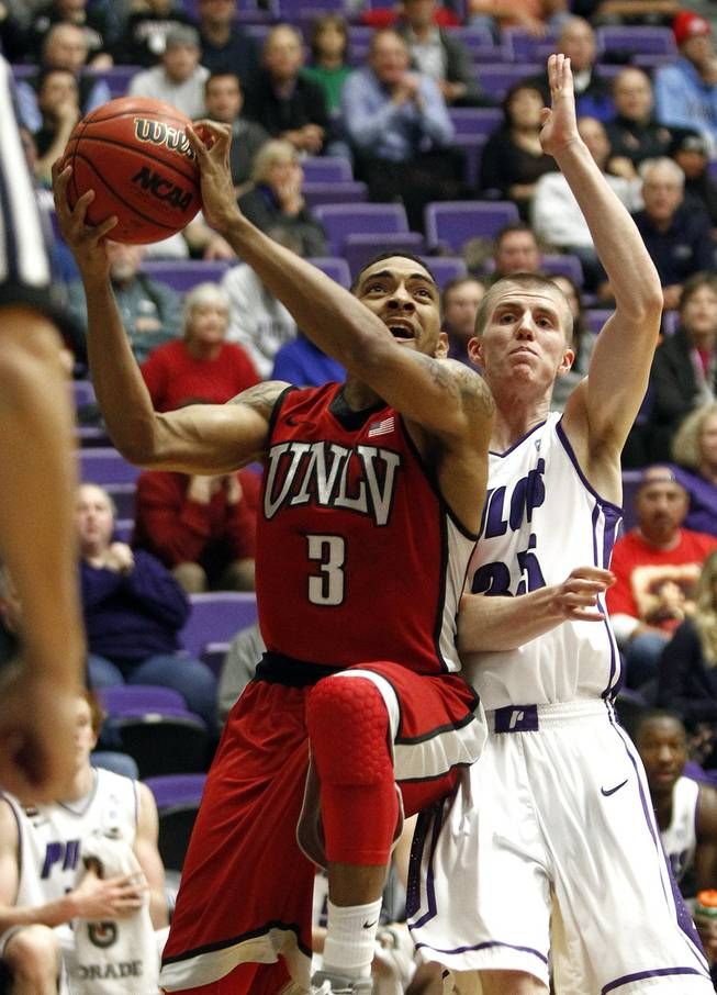 UNLV guard Anthony Marshall, left, goes to the basket past Portland guard David Carr during the first half of a game in Portland, Ore., Tuesday, Dec. 4, 2012.