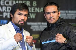 Filipino boxer Manny Pacquiao, left, and Juan Manuel Marquez of Mexico pose during a news conference at the MGM Grand Wednesday, Dec. 5, 2012. Pacquiao and Marquez will fight for a fourth time in a welterweight bout at the MGM Grand Garden Arena Saturday.