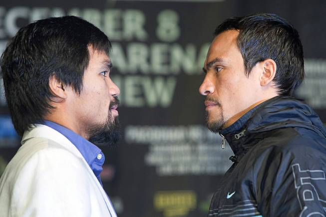 Filipino boxer Manny Pacquiao, left, and Juan Manuel Marquez of Mexico face off during a news conference at the MGM Grand Wednesday, Dec. 5, 2012. Pacquiao and Marquez will fight for a fourth time in a welterweight bout at the MGM Grand Garden Arena Saturday.