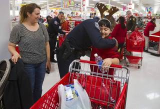North Las Vegas Police officer Marcus Cook gives a hug to Leonardo Solis as his mother Eida Gonzalez looks on during an annual Shop With A Cop event at the Target store at 2189 W. Craig Rd. in North Las Vegas, Wednesday, December 5, 2012.