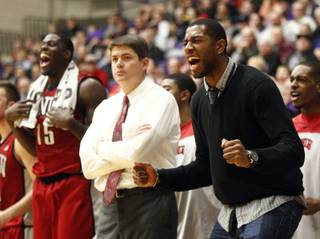 UNLV players Mike Moser, right, and Anthony Bennett, left, celebrate from the bench on both sides of coach Dave Rice during the second half of their game in Portland, Ore., Tuesday, Dec. 4, 2012. Bennett led UNLV in scoring with 18 points as they won 68-60.