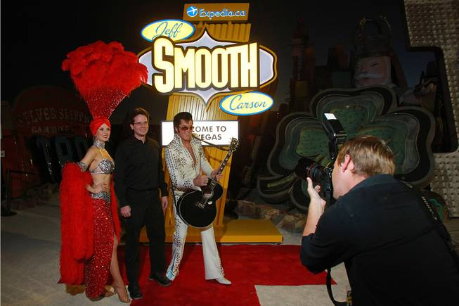 Showgirl Jennifer Autry and Elvis impersonator Brendan Paul pose for a photo with contest winner Jeff Paul during an event to honor Paul who won an Expedia.ca contest Thursday, Dec. 6, 2012 at the Neon Museum.
