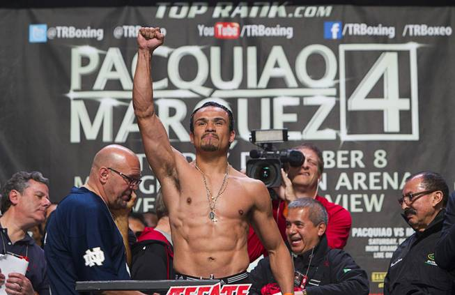 Mexican boxer Juan Manuel Marquez poses on the scale during an official weigh-in at the MGM Grand Friday, Dec. 7, 2012. Marquez will take on Filipino boxer Manny Pacquiao for the fourth time in a welterweight bout at the arena on Saturday.