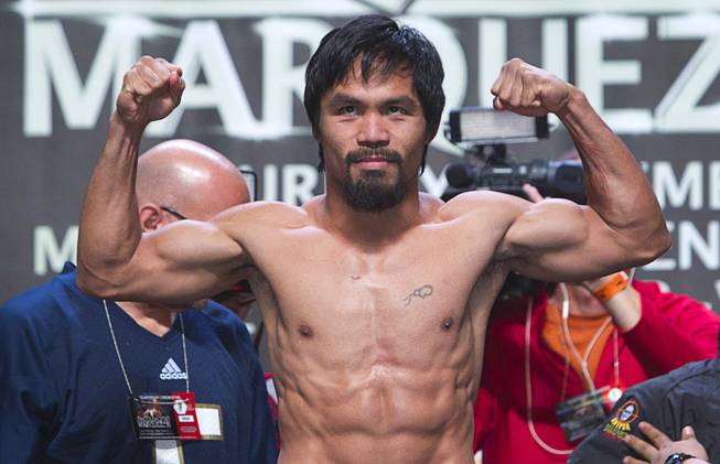 Filipino boxer Manny Pacquiao flexes on the scale during an official weigh-in at the MGM Grand Garden Arena Friday, Dec. 7, 2012. Pacquiao will take on Juan Manuel Marquez of Mexico for the fourth time in a welterweight bout at the arena on Saturday.