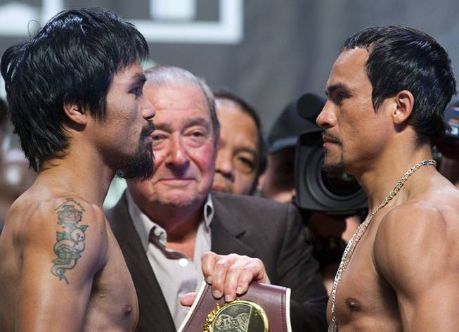 Filipino boxer Manny Pacquiao, left, and Juan Manuel Marquez of Mexico face off during an official weigh-in at the MGM Grand Garden Arena Friday, Dec. 7, 2012. Pacquiao and Marquez will fight for the fourth time in a welterweight bout at the arena on Saturday. Boxing promoter Bob Arum looks on at center left.