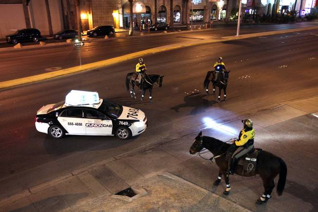 The Las Vegas Metropolitan Police Mounted Unit pulls over a taxi on Harmon Avenue just east of the Las Vegas Strip on Friday, December 7, 2012.