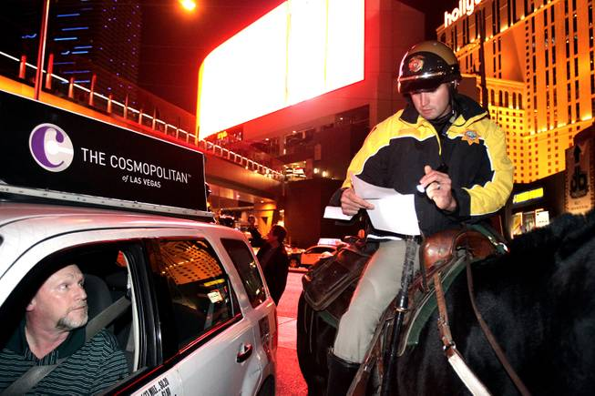 Officer Tim Ruiz of the Las Vegas Metropolitan Police Mounted Unit talks to a taxi driver they pulled over on Harmon Avenue just east of the Las Vegas Strip on Friday, December 7, 2012.