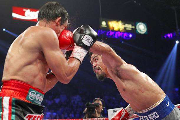 Manny Pacquiao (R) of the Philippines lands a punch on Juan Manuel Marquez of Mexico during their welterweight fight at the MGM Grand Garden Arena in Las Vegas, Nevada December 8, 2012. Marquez went on to win with a sixth-round knockout.