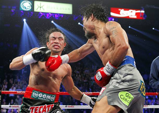 Juan Manuel Marquez (L) of Mexico takes a punch from Manny Pacquiao of the Philippines during their welterweight fight at the MGM Grand Garden Arena in Las Vegas, Nevada December 8, 2012. Marquez went on to win with a sixth-round knockout.