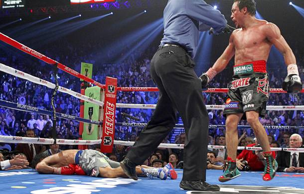 Juan Manuel Marquez is directed to a neutral corner after knocking out Manny Pacquiao during the sixth round of their welterweight fight at MGM Grand Garden Arena on Saturday, Dec. 8, 2012.