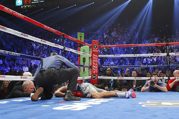 Referee Kenny Bayless looks over Manny Pacquiao of the Philippines after he was knocked out by Juan Manuel Marquez of Mexico during their welterweight fight at the MGM Grand Garden Arena in Las Vegas, Nevada December 8, 2012.