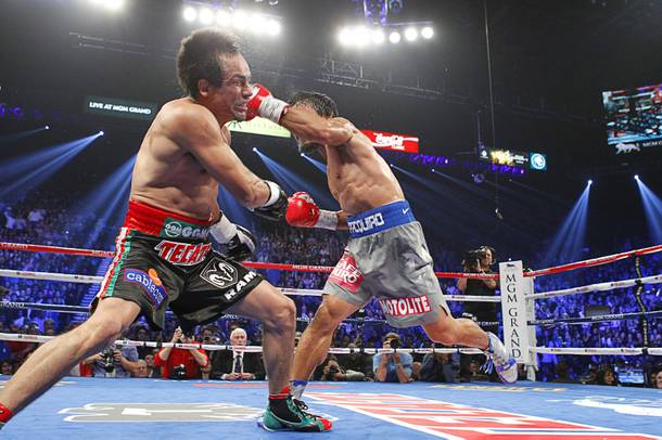 Juan Manuel Marquez (L) of Mexico takes a hit from Manny Pacquiao of the Philippines during their welterweight fight at the MGM Grand Garden Arena in Las Vegas, Nevada December 8, 2012.