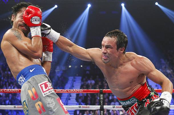 Manny Pacquiao (L) of the Philippines takes a punch from Juan Manuel Marquez of Mexico during their welterweight fight at the MGM Grand Garden Arena in Las Vegas, Nevada December 8, 2012.