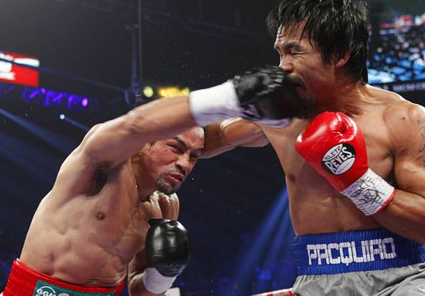 Juan Manuel Marquez (L) of Mexico connects on Manny Pacquiao of the Philippines during their welterweight fight at the MGM Grand Garden Arena in Las Vegas, Nevada December 8, 2012.