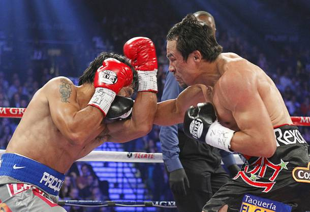 Manny Pacquiao (L) of the Philippines fights Juan Manuel Marquez of Mexico during their welterweight fight at the MGM Grand Garden Arena in Las Vegas, Nevada December 8, 2012.