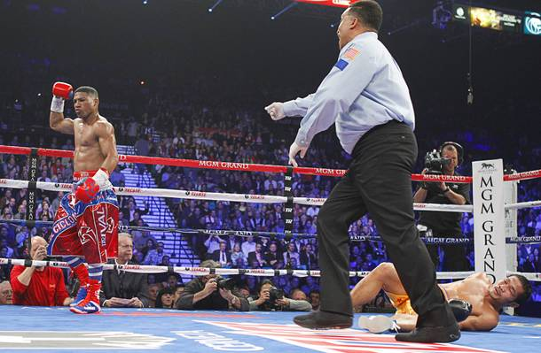 Yuriorkis Gamboa (L) of Cuba is sent to his neutral corner by referee Tony Weeks after knocking down Michael Farenas of the Philippines during their WBA interim super featherweight fight at the MGM Grand Garden Arena in Las Vegas, Nevada December 8, 2012.