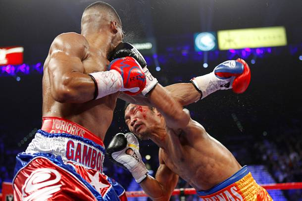 Yuriorkis Gamboa (L) of Cuba takes a punch from Michael Farenas of the Philippines during their WBA interim super featherweight fight at the MGM Grand Garden Arena in Las Vegas, Nevada December 8, 2012.