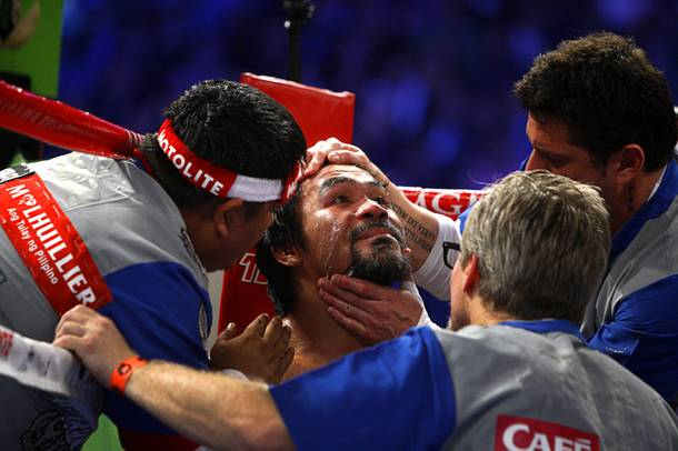 Manny Pacquiao of the Philippines is treated by his corner between rounds during his welterweight fight against Juan Manuel Marquez of Mexico at the MGM Grand Garden Arena in Las Vegas, Nevada December 8, 2012.