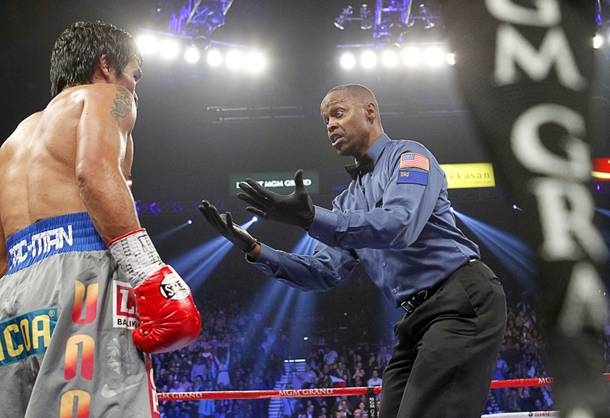 Referee Kenny Bayless gestures to Manny Pacquiao of the Philippines after Pacquiao was knocked down by Juan Manuel Marquez of Mexico in the third round of their welterweight fight at the MGM Grand Garden Arena in Las Vegas, Nevada December 8, 2012.