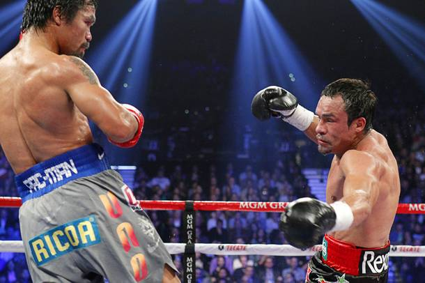 Manny Pacquiao of the Philippines watches as Juan Manuel Marquez of Mexico is knocked down in the fifth round of their welterweight fight at the MGM Grand Garden Arena in Las Vegas, Nevada December 8, 2012.