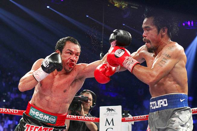Juan Manuel Marquez (L) of Mexico punches at Manny Pacquiao of the Philippines during their welterweight fight at the MGM Grand Garden Arena in Las Vegas, Nevada December 8, 2012.