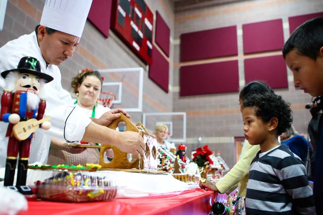 "Children, from right, Tony Castillo and Anthony Cherry watch Chef Jesus Castillo create a gingerbread house during the ""We Knead the Dough"" festival at Faith Lutheran School campus Saturday, December 8, 2012."
