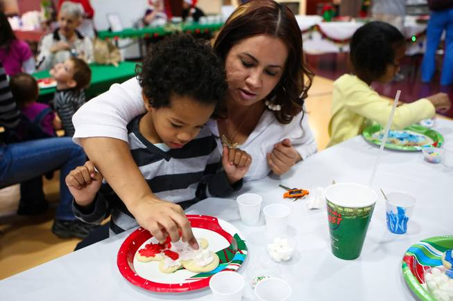 "Anthony Cherry, 5, receives a little help from his mom, Regina Zamora, while making his gingerbread man at the ""We Knead the Dough"" festival at Faith Lutheran School campus Saturday, December 8, 2012."
