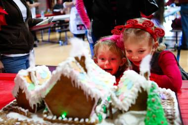 "Addison Gerber, 2, reacts with excitement while checking out the gingerbread houses with her friend, Sohayla Henry, 4, right, at the ""We Knead the Dough"" festival at Faith Lutheran School campus Saturday, December 8, 2012."