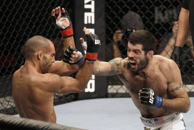 Matt Brown, right, punches Mike Swick in the second round during a welterweight mixed martial arts bout at a UFC on FOX event in Seattle, Saturday, Dec. 8, 2012. Brown won by knockout in the second round.