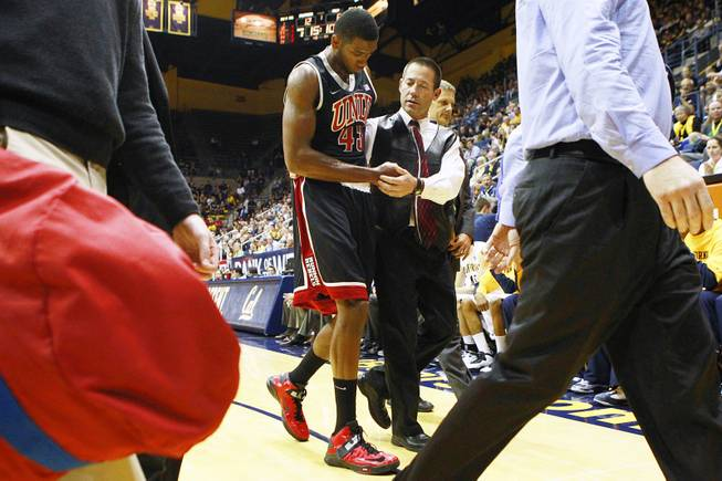 UNLV trainer Dave Tomchek leads forward Mike Moser off the floor after a Cal player fell on his arm during the first half of their game Sunday, Dec. 9, 2012 at Haas Pavilion in Berkeley, Calif.