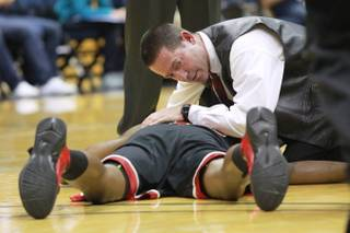 Trainer Dave Tomchek assess UNLV forward Mike Moser's injury during the first half of their game Sunday, Dec. 9, 2012 at Haas Pavilion in Berkeley, Calif. Moser came out of the game with a dislocated elbow. UNLV won 76-75.