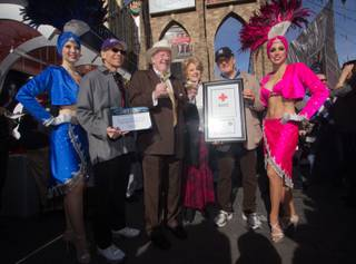 Michael Severino, former Las Vegas Mayor Oscar Goodman, current Las Vegas Mayor Carolyn Goodman and Larry Ruvo pose for a picture with two showgirls at the Start Spreadin the News, fundraiser event held at  New York-New York Hotel & Casino's Brooklyn Bridge,