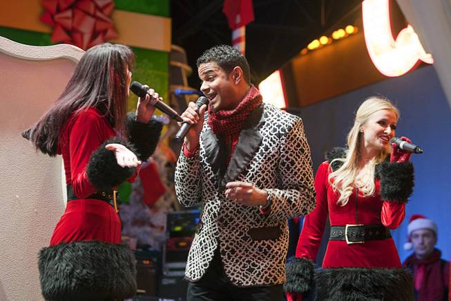 Members of Candy and the Canes, from left, Renee Warden, Hunter Gerarade, and Becca Kotte perform during a Christmas tree lighting ceremony at the Fremont Street Experience in downtown Las Vegas Monday, Dec. 10, 2012.
