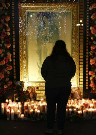 Fan Jenny Guerrero pays tribute to singer Jenni Rivera at a makeshift memorial in front of an image of the Virgin of Guadalupe at the Plaza Mexico shopping center in Lynwood, Calif., early Monday, Dec. 10, 2012.