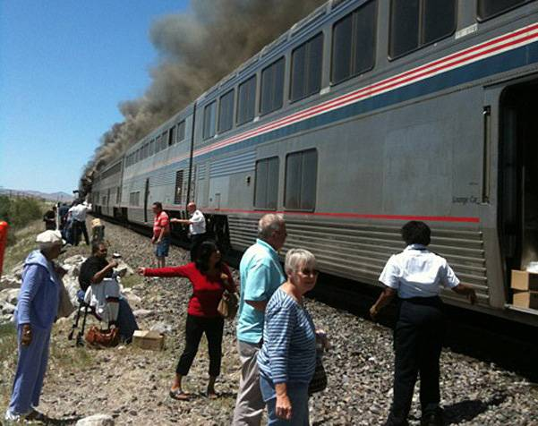 In this photo provided by Ron Almgren, passengers and Amtrak train staff are seen at the site of a collision between an Amtrak westbound train and a truck on  U.S. 95 about four miles south of Interstate 80 on Friday, June 24, 2011, about 70 miles east of Reno, Nev.